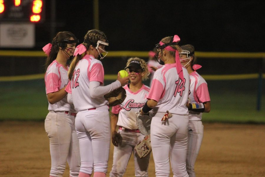 The Lady Lancers celebrate on the mound during the annual Pink Game on Sept. 23, where they won over the Marquette Mustangs 5-2. This year, the game was in honor of language arts teacher Jenny Ingram.