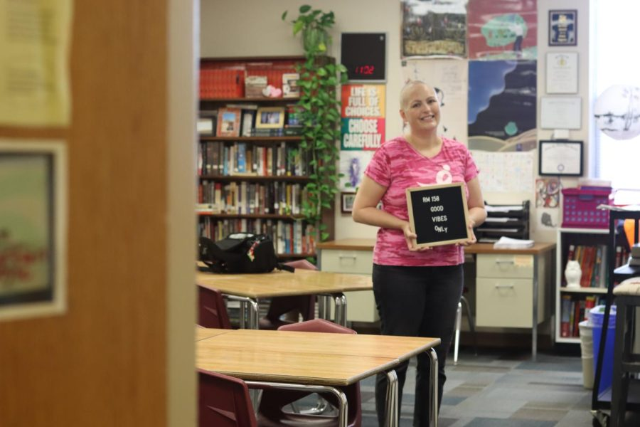 Language arts teacher Jenny Ingram stands in her classroom holding her Good Vibes Only sign. In June 2021 Ingram learned that her Breast Cancer resurfaced as Stage Four. She has since made an effort to maintain a positive perspective.
