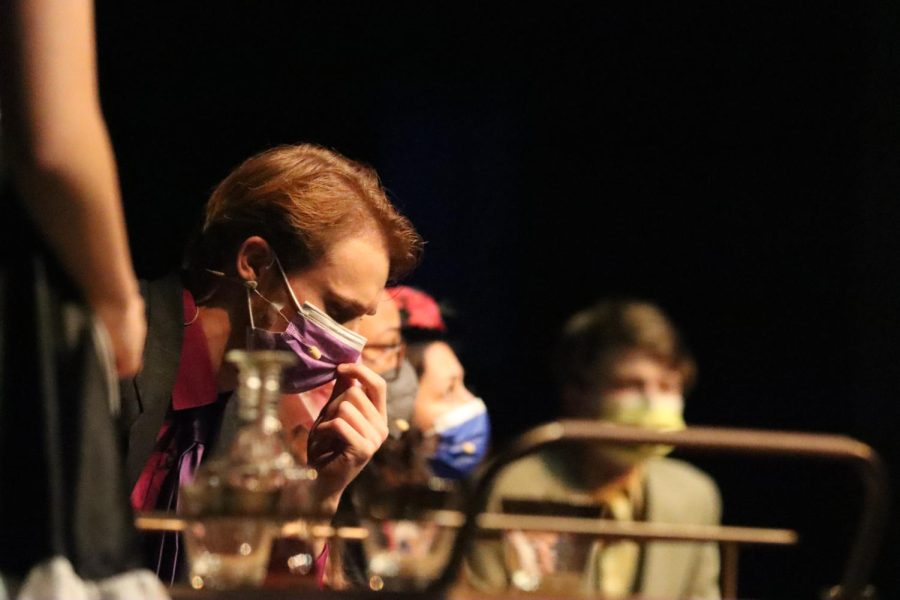 As Yvette, the maid, played by Mallory Gabris, serves drinks towards the beginning of the play, Professor Plum, played by senior Peter Schaper, ponders with the rest of the characters why they were invited to the dinner party.