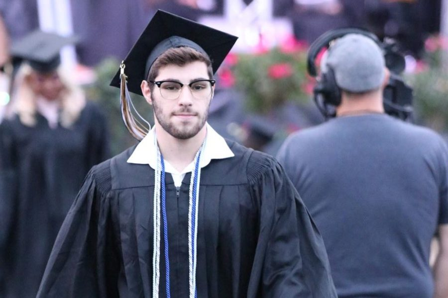 Noah Hindi, class of 2021, walks back to his seat after receiving his certificate on June 2. In previous years, Graduation was at Chaifetz Arena on St. Louis Universitys (SLU) Campus, but because of COVID-19, SLU cancelled its events. As a result, the 2021 Graduation was held at the POWERplex.