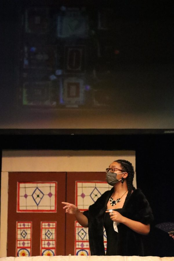 Cazembes character, Mrs. White questions Bounds character, Wadsworth, as he explains the basis of the play, the board game Clue. The image projected on the screen represents the rooms throughout the house.